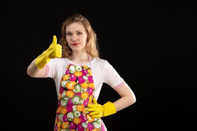 Een vooraanzicht jong aantrekkelijk meisje in kleurrijke kaap die dragend gele handschoenen glimlachen die ontzagwekkend teken op de zwarte positiviteit van de achtergrondliefdeglimlach tonen