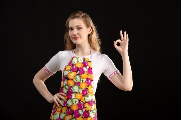 Een vooraanzicht jong aantrekkelijk meisje in kleurrijke kaap die tonend tekens op de zwarte schoonmakende huisvrouw glimlachen als achtergrond