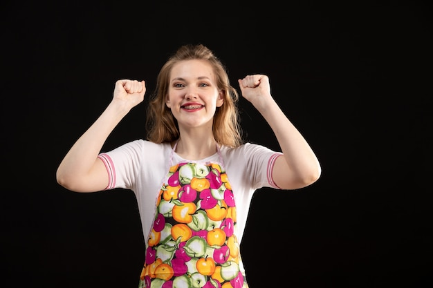 Een vooraanzicht jong aantrekkelijk meisje in kleurrijke opgewekte kaap gelukkig op de zwarte schoonmakende huisvrouw als achtergrond
