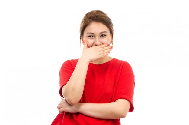 Een vooraanzicht jong aantrekkelijk meisje in rode t-shirt die zwarte jeans dragen die gelukkig op het wit lachen