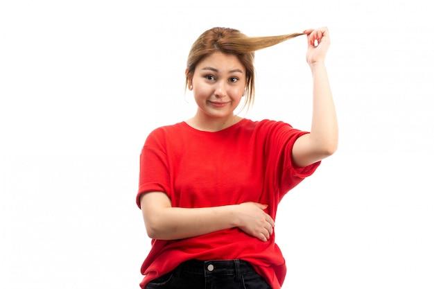 Een vooraanzicht jong aantrekkelijk meisje in rode t-shirt die zwarte jeans dragen die haar haar op het wit trekken