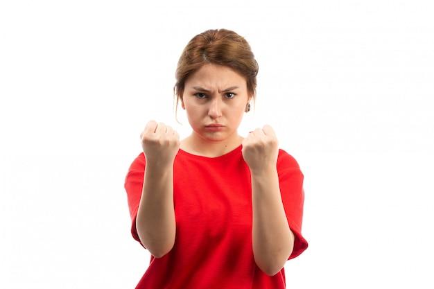 Een vooraanzicht jong aantrekkelijk meisje in rode t-shirt die zwarte jeans dragen die met vuist op het wit bedreigen