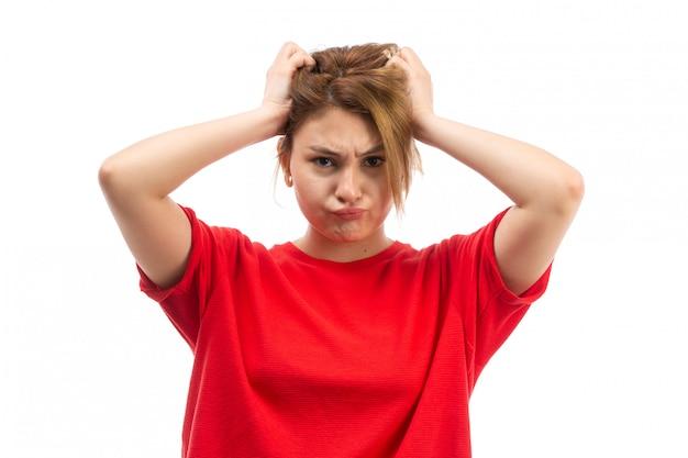 Een vooraanzicht jong aantrekkelijk meisje in rode t-shirt die zwarte jeans dragen wat betreft haar haar op het wit