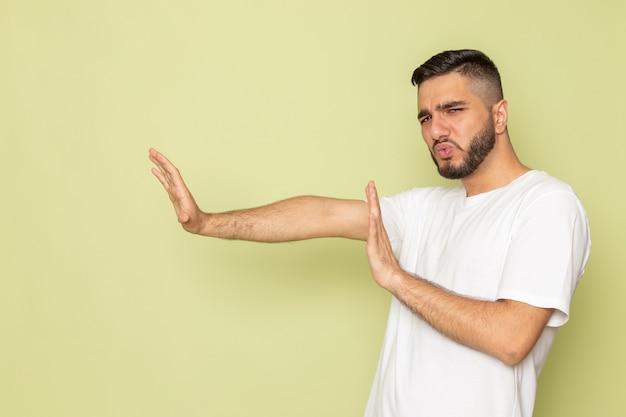 Een vooraanzicht jong mannetje in wit t-shirt dat sociale regels op afstand houdt