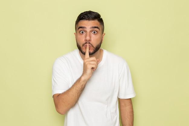 Een vooraanzicht jong mannetje in wit t-shirt dat stilte teken toont