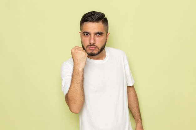 Een vooraanzicht jong mannetje in wit t-shirt dat zijn vuist toont