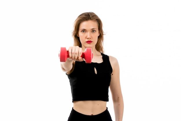 Een vooraanzicht jong meisje in zwart overhemd en zwarte broeken die sport met rode domoren op het wit doen