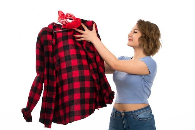 Een vooraanzicht jong mooi meisje dat in blauw t-shirt en jeans rood-zwart geruit overhemd houdt glimlachend op het wit