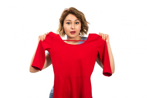 Een vooraanzicht jong mooi meisje in blauw overhemd en jeans die rode kleding op het wit meten