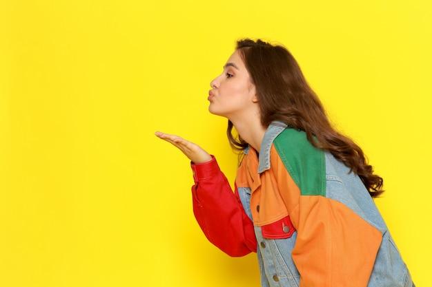 Een vooraanzicht jong mooi meisje in rode overhemdlaag en jeans die luchtkussen verzenden