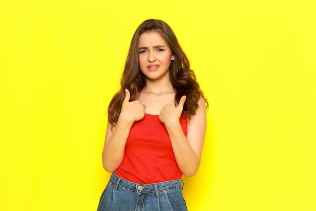 Een vooraanzicht jong mooi meisje in rood overhemd en jeans die met ontevreden uitdrukking stellen
