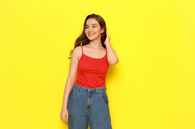 Een vooraanzicht jong mooi meisje in rood overhemd en jeans enkel die zich met glimlach bevinden