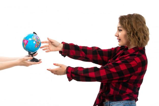 Een vooraanzicht jong mooi meisje in rood-zwart geruit overhemd en spijkerbroek die kleine wereldbol op de witte