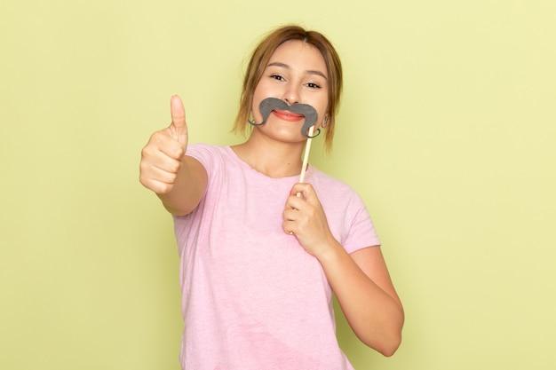 Een vooraanzicht jong mooi meisje in roze t-shirt spijkerbroek poseren met nep snor en lachend op groen
