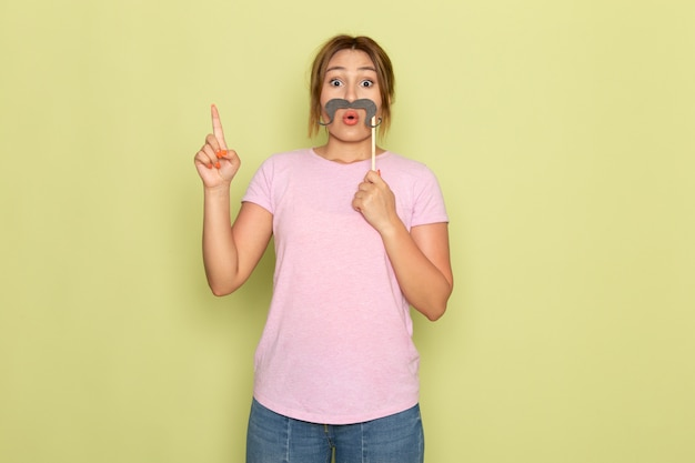 Een vooraanzicht jong mooi meisje in roze t-shirt spijkerbroek poseren met nep snor op groen