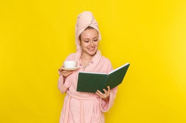 Een vooraanzicht jong mooi wijfje dat in roze badjas groen voorbeeldenboek en kop thee houdt