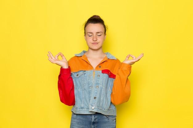 Een vooraanzicht jong wijfje in geel overhemd kleurrijk jasje en jeans het mediteren