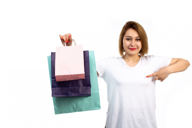 Een vooraanzicht jong wijfje in wit t-shirt en zwarte jeans die verschillende gekleurde het winkelen pakketten houden glimlachend op het wit