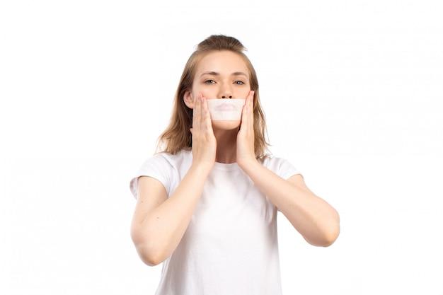 Een vooraanzicht jong wijfje in wit t-shirt met wit verband rond haar mond op het wit