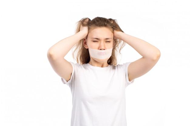Een vooraanzicht jong wijfje in wit t-shirt met wit verband rond haar mond wat betreft haar haar boos op het wit