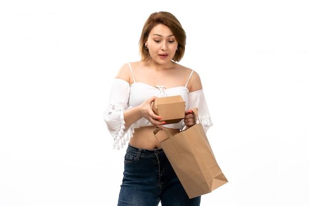 Een vooraanzicht jonge aantrekkelijke dame die in wit overhemd en jeans bruin pakket houdt glimlachend op het wit