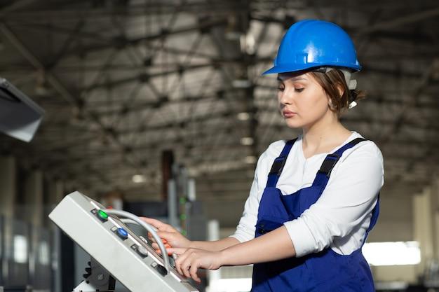 Een vooraanzicht jonge aantrekkelijke dame in blauw bouwkostuum en helm controlerende machines in hangaar die overdag gebouwenarchitectuurbouw werken