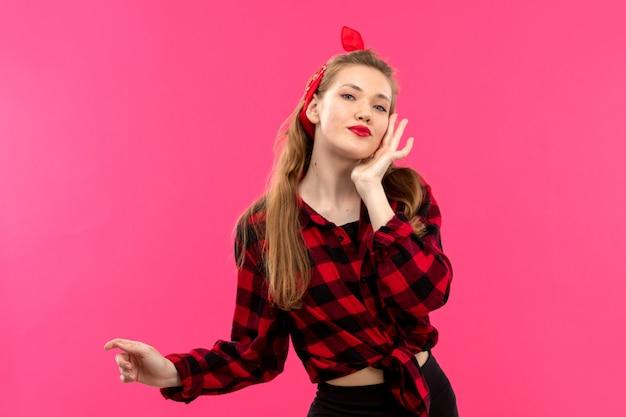 Een vooraanzicht jonge aantrekkelijke dame in geruit rood-zwart shirt zwarte broek poseren op de roze achtergrond jonge vrouwelijke mode