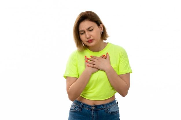 Een vooraanzicht jonge aantrekkelijke dame in groen overhemd en spijkerbroek die aan ademhalingsproblemen op het wit lijden