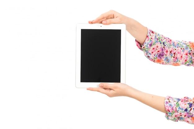 Een vooraanzicht jonge aantrekkelijke dame in kleurrijk bloem ontworpen overhemd dat witte tablet op het wit houdt