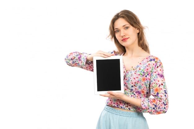 Een vooraanzicht jonge aantrekkelijke dame in kleurrijk bloem ontworpen overhemd en blauwe rok die witte tablet op het wit houden