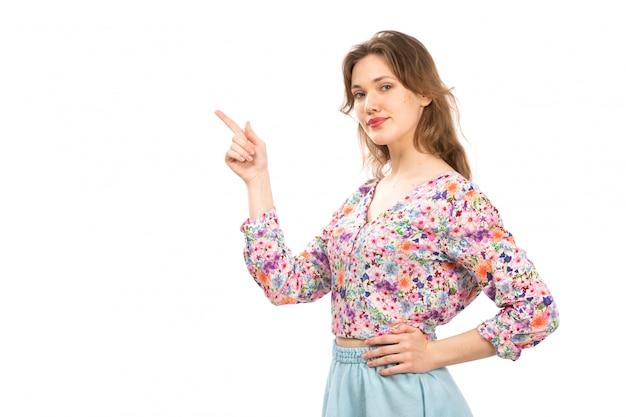 Een vooraanzicht jonge aantrekkelijke dame in kleurrijke bloem ontworpen overhemd en blauwe rok op de witte