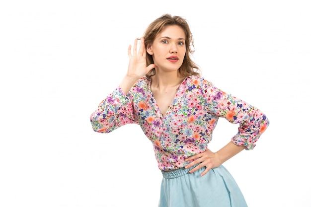Een vooraanzicht jonge aantrekkelijke dame in kleurrijke bloem ontworpen overhemd en blauwe rok poseren op de witte