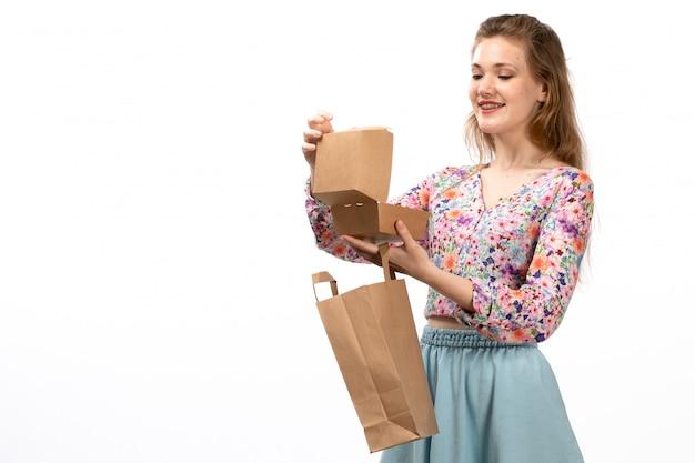 Een vooraanzicht jonge aantrekkelijke dame in kleurrijke bloem ontworpen shirt en blauwe rok bruin pakket en doos lachend op de witte