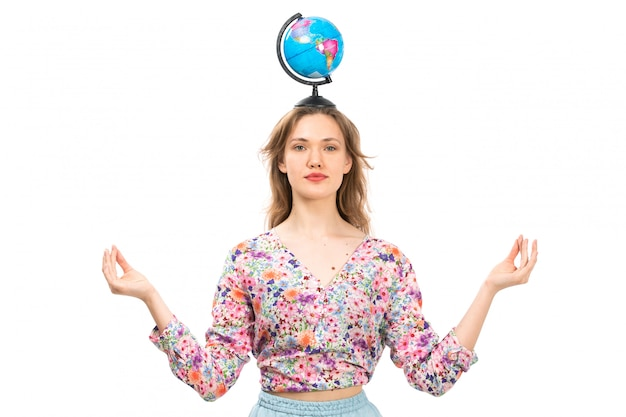 Een vooraanzicht jonge aantrekkelijke dame in kleurrijke bloem ontworpen shirt en blauwe rok met kleine wereldbol op haar hoofd mediteren op het wit