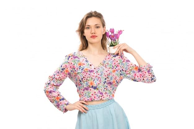 Een vooraanzicht jonge aantrekkelijke dame in kleurrijke bloem ontworpen shirt en blauwe rok met paarse bloem plant op de witte