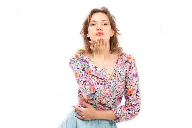 Een vooraanzicht jonge aantrekkelijke dame in kleurrijke bloem ontworpen shirt en blauwe rok poseren lucht kusjes verzenden op de witte
