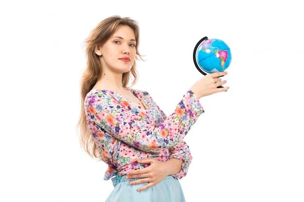 Een vooraanzicht jonge aantrekkelijke dame in kleurrijke bloemen ontworpen shirt en blauwe rok met kleine wereldbol op het wit