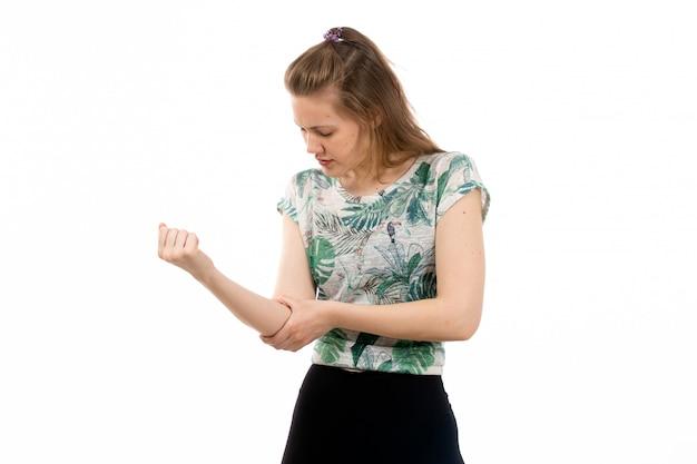 Een vooraanzicht jonge aantrekkelijke dame in ontworpen overhemd en zwarte broek die aan armpijn op het wit lijden