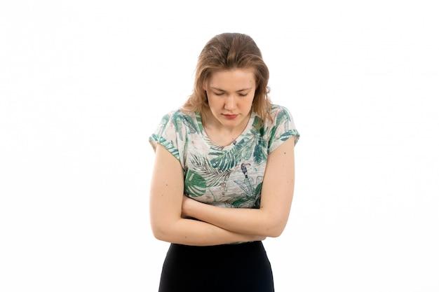 Een vooraanzicht jonge aantrekkelijke dame in ontworpen overhemd en zwarte broek die lijden aan buikpijn op de witte