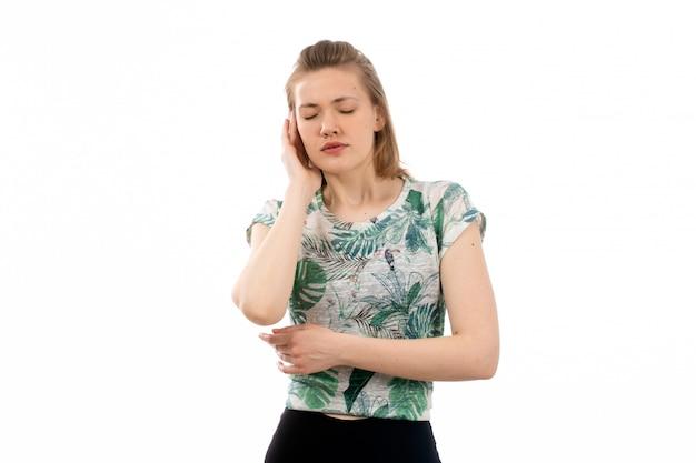 Een vooraanzicht jonge aantrekkelijke dame in ontworpen overhemd en zwarte broek die lijden aan hoofdpijn op de witte