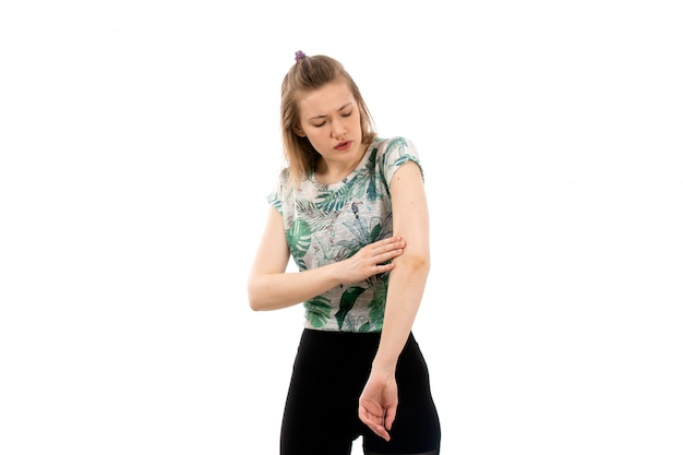 Een vooraanzicht jonge aantrekkelijke dame in ontworpen overhemd en zwarte broek die lijden aan pijn in de arm op de witte