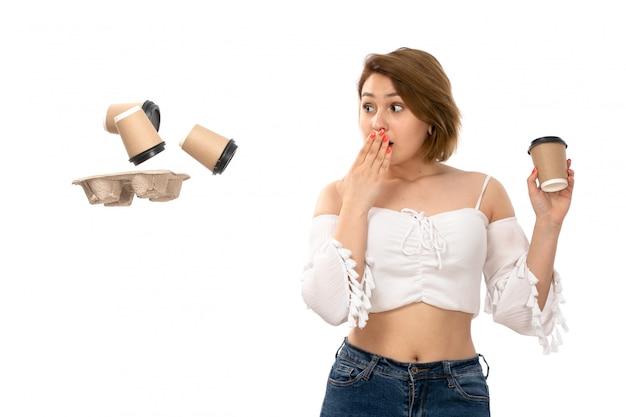 Een vooraanzicht jonge aantrekkelijke dame in wit overhemd en spijkerbroek koffiekopjes gooien verrast op het wit