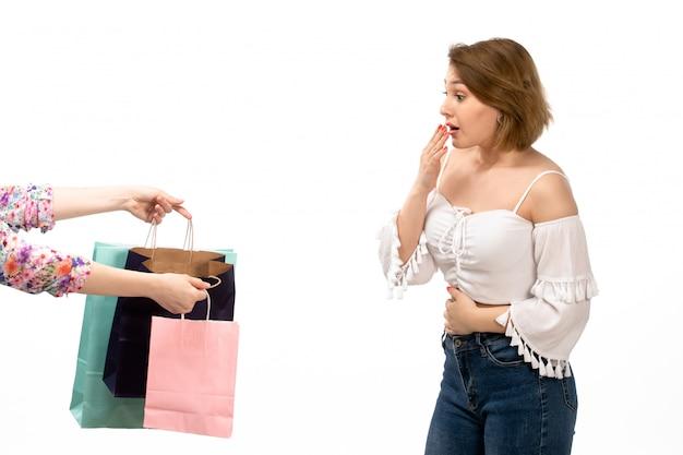 Een vooraanzicht jonge aantrekkelijke dame in wit overhemd en spijkerbroek krijgen shopping pakketten op de witte