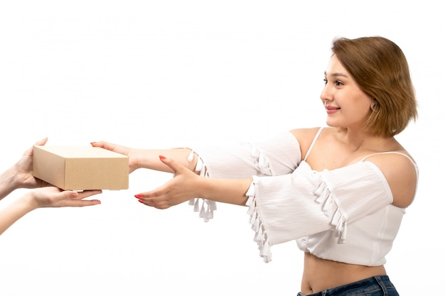 Een vooraanzicht jonge aantrekkelijke dame in wit overhemd en spijkerbroek krijgt weinig pakket op de witte