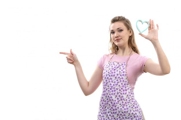 Een vooraanzicht jonge aantrekkelijke huisvrouw in het roze overhemd kleurrijke kaap stellen die glimlachend houdend weinig blauwe hartvorm op het witte wijfje van de achtergrondkeukenkeuken glimlachen