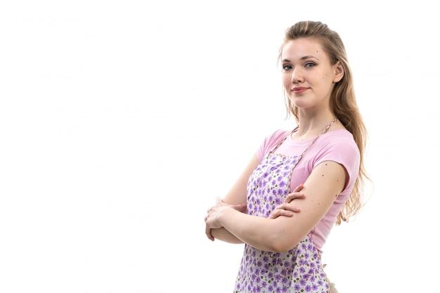 Een vooraanzicht jonge aantrekkelijke huisvrouw in roze overhemd het kleurrijke kaap het glimlachen stellen op het witte wijfje van de achtergrondkeukenkeuken