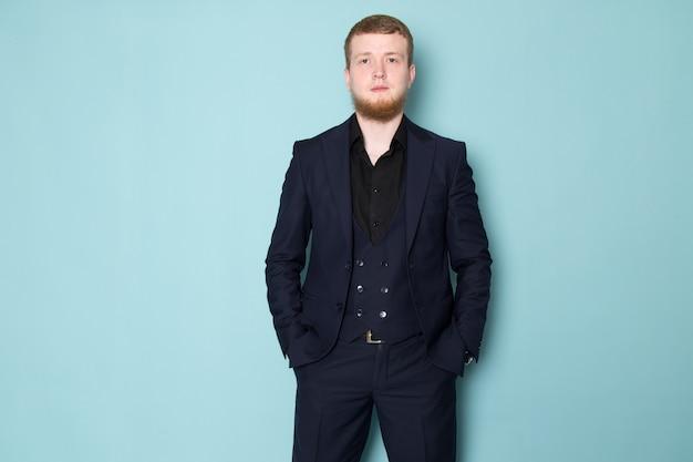 Een vooraanzicht jonge aantrekkelijke man in zwart donker klassiek modern pak met baard op de blauwe ruimte