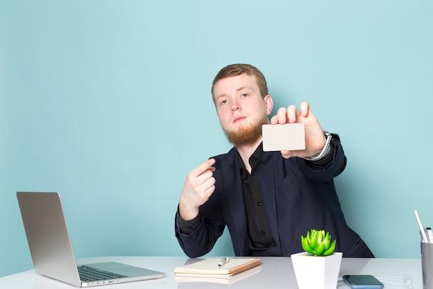 Een vooraanzicht jonge aantrekkelijke man met baard in zwart donker klassiek modern pak met behulp van laptop met witte kaart op de blauwe ruimte