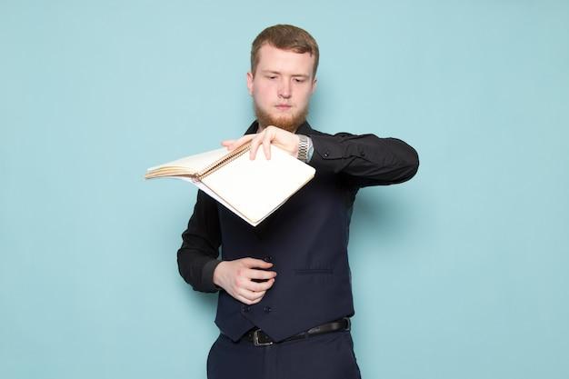 Een vooraanzicht jonge aantrekkelijke man met baard in zwart donker klassiek modern pak met bestanden kijken naar zijn polshorloge op de blauwe ruimte