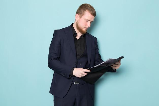 Een vooraanzicht jonge aantrekkelijke man met baard in zwart donker klassiek modern pak met zwart lederen map op de blauwe ruimte